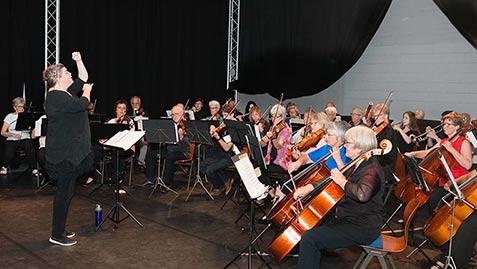 Deventer Symfonisch Orkest tijdens een concert in het havenkwartier te Deventer. Te zien zijn de celli en de dirigent.